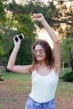 年轻时髦的逗人喜爱的女孩听到在耳机的音乐在手机并且在公园跳舞 俏丽的妇女放松和 免版税图库摄影