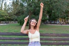年轻时髦的逗人喜爱的女孩听到在耳机的音乐在手机并且在公园跳舞 俏丽的妇女放松和 免版税库存图片