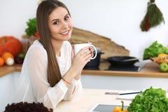年轻愉快的妇女在厨房里拿着白色杯子并且看照相机,当坐在木桌上在中时 图库摄影
