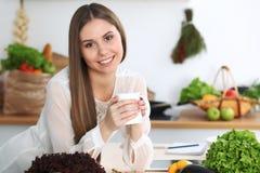 年轻愉快的妇女在厨房里拿着白色杯子并且看照相机,当坐在木桌上在中时 免版税库存照片