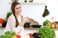 年轻愉快的妇女在厨房里拿着白色杯子并且看照相机,当坐在木桌上在中时 免版税库存图片