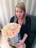 年轻性感的白肤金发的女孩在有玫瑰花箱子大花束的屋子里  图库摄影