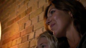年轻白种人女性特写镜头画象和她的与平安的表情一起的女儿看着电视 影视素材