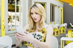 年轻白肤金发的妇女在震动起反应对手机文本照片表示 免版税库存照片