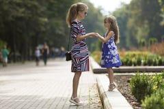 年轻白肤金发的妇女和小儿童女孩握手在晴朗的公园胡同的时兴的礼服的 库存照片