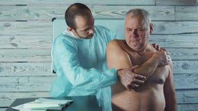 年轻生理治疗师与诊所的资深患者一起使用 疼痛胳膊的考试 股票视频
