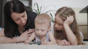 年轻获得母亲和两个的孩子与片剂计算机的乐趣在地板上在家,生活方式 影视素材