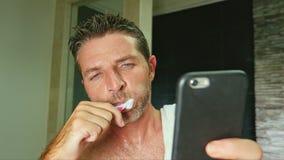 年轻英俊和有吸引力的互联网上瘾者人在家卫生间画象有毛巾的在肩膀洗涤的牙与 免版税库存图片