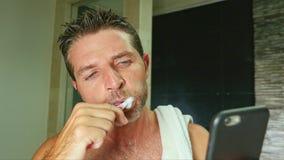 年轻英俊和有吸引力的互联网上瘾者人在家卫生间画象有毛巾的在肩膀洗涤的牙与 免版税库存照片