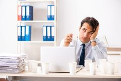 年轻雇员使上瘾对咖啡 免版税库存图片