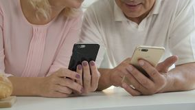年长男性举行的电话和在家使用智能手机的资深妇女 股票视频