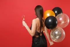 庆祝的年轻女人后面背面图黑礼服的,拿着杯香槟,在红色隔绝的气球 图库摄影