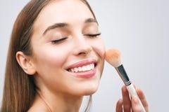 应用化妆用品的妇女 图库摄影