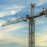 建筑反对明亮的多云天空的塔吊 免版税库存图片