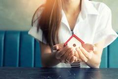 建筑学、大厦、建筑、房地产和物产概念-接近拿着房子模型的手 房屋贷款物产 免版税图库摄影