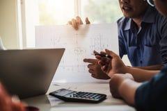 建筑师或工程师队与建立计划设计项目的图纸一起使用在办公室建筑工程师工具和 免版税库存图片