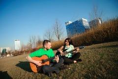 弹吉他的浪漫年轻夫妇画象在天空蔚蓝下 免版税库存图片