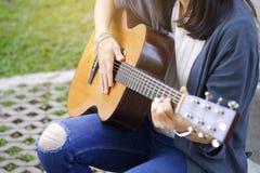 弹声学吉他的妇女在庭院里 免版税库存图片