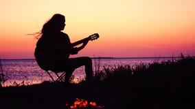 弹在海滩的少女吉他与营火在日落 影视素材