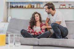 开心和看在沙发的年轻夫妇后面看法电视在客厅 人妇女年轻人 免版税图库摄影