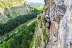 Żeńscy arywista zmiany carabiners na a przez ferrata trasy, pionowo ścienna wysokość nad dolina z drogą za, zdjęcie stock