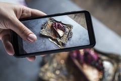 Żeńska ręka z menchiami robi manikiur fotografie na telefonu kawałku tort na złocistej tacy fotografia royalty free