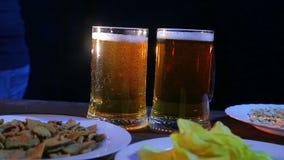 Żeński barman stawia stół z przekąskami na czarnym tle dwa dalej folował kubki pieniący piwo zdjęcie wideo