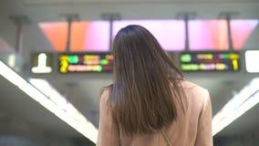 Żeński dojeżdżający patrzeje rozkład na stacji kolejowej, turysta w nowym mieście zbiory wideo
