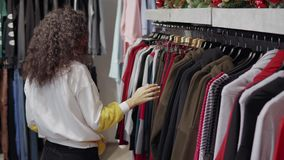 Żeński klient robi zakupy na sklepie odzieżowym i patrzeje na stojakach, uśmiechnięty zdjęcie wideo