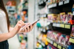 Żeński klient z telefonem w ręce, sklep spożywczy obrazy stock