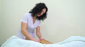 Żeński masażysta w jednolitej masowanie mężczyzny goleni w zdroju salonie zbiory