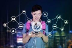 Żeński uczeń używa telefon z 5G siecią zdjęcie royalty free