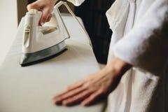 Żeńskich ręki prasowania ubrań odgórny widok odizolowywający na białym tle Młoda kobieta z żelazną prasowanie mężczyzny koszula w obraz royalty free