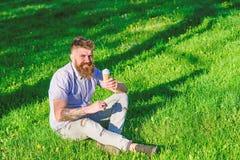 当坐草时,有长的胡子的人享用冰淇凌 纤巧概念 有胡子的在愉快的面孔的人和髭 库存照片