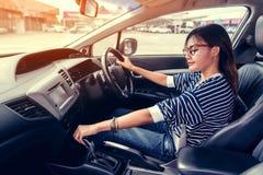 当她专心地时,是在汽车亚裔妇女使用汽车齿轮今后驾驶 免版税库存图片