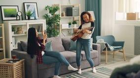 当她的亚裔朋友记录有智能手机的录影和时,逗人喜爱的非裔美国人的妇女在家弹吉他 影视素材