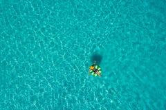 微小的妇女游泳鸟瞰图在游泳圆环多福饼的在透明绿松石海在塞舌尔 夏天海景与 免版税库存照片