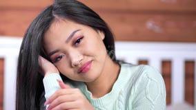 微笑嬉戏的年轻亚裔的女孩画象接触头发和看照相机 股票视频