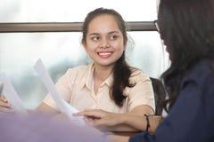 微笑对工作采访,与妇女工友的女性谈话的年轻亚裔妇女在办公室 库存照片