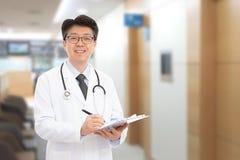 微笑在医院的背景中的亚裔男性医生 库存图片