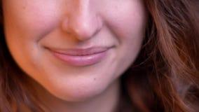 微笑入在被弄脏的光背景的照相机的年轻白种人女孩特写镜头嘴唇画象  股票视频
