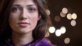 微笑和摆在与是她的头发的照相机前面的年轻俏丽的白种人女性模型特写镜头画象  影视素材