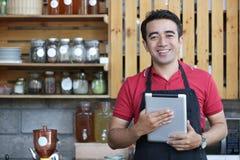 微笑和摆在咖啡馆酒吧里面和微笑对照相机的一个愉快的亚洲可爱的男性,当拿着片剂计算机时 免版税图库摄影
