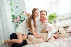 微笑和笑,摆在照相机和拥抱的可爱的家庭为全家福 库存照片