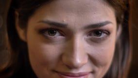 微笑和看与不信任的年轻美丽的白种人女性特写镜头画象照相机 影视素材