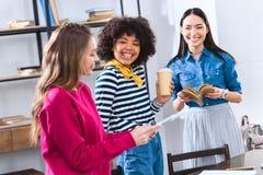 微笑的多文化学生选择聚焦有片剂书和咖啡的 免版税库存照片