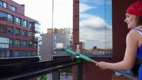 微笑的妇女干净的窗口在家庭阳台上 愉快的怀孕的女孩整洁的玻璃 股票视频