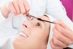 微笑的妇女得到眼眉治疗 免版税库存照片