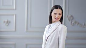 微笑的年轻女实业家画象在白色豪华背景中的摆在和看照相机 影视素材