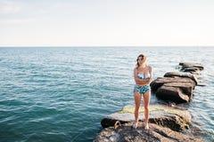 微笑的年轻女性模型室外射击在站立反对蓝天的比基尼泳装的 获得的妇女乐趣在夏日 免版税图库摄影